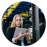 Female walking through datacentre with tablet.