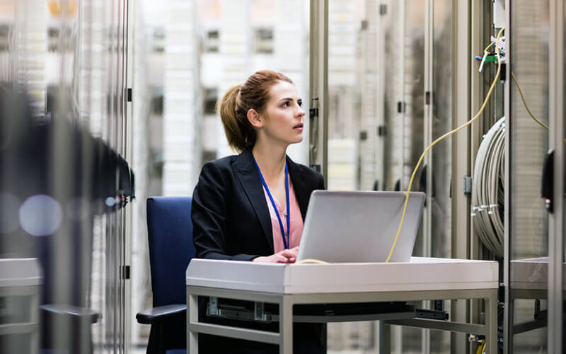 Woman on laptop in server room data center