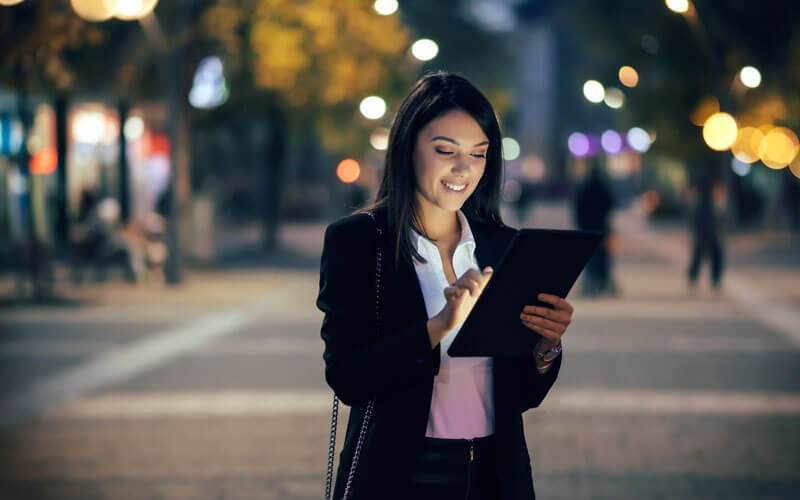 Business woman in street at night using tablet