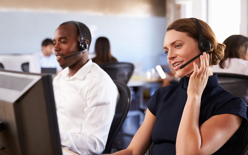 IT support experts on headsets wait to take calls in Remote Network Operations Center