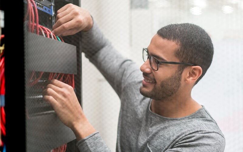 Smiling IT professional reaches for cables in data center
