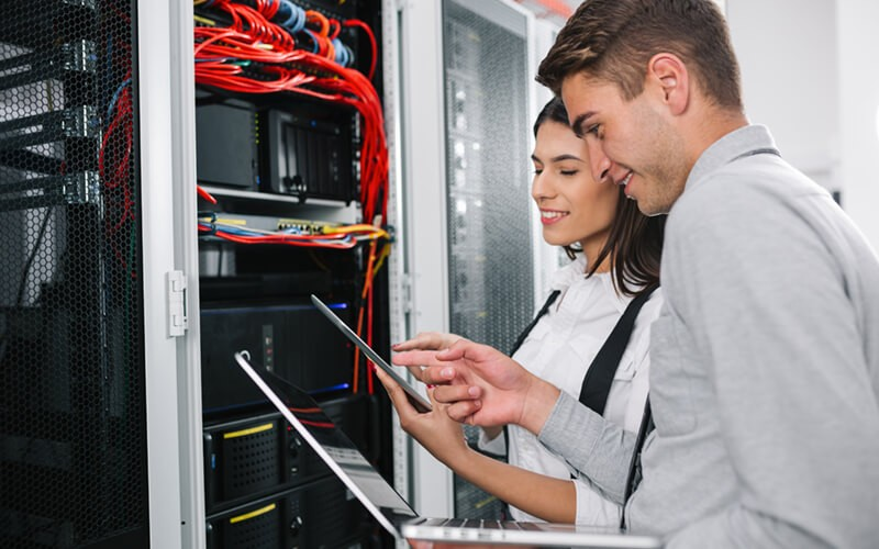 Two IT engineers on-site in data center with laptop