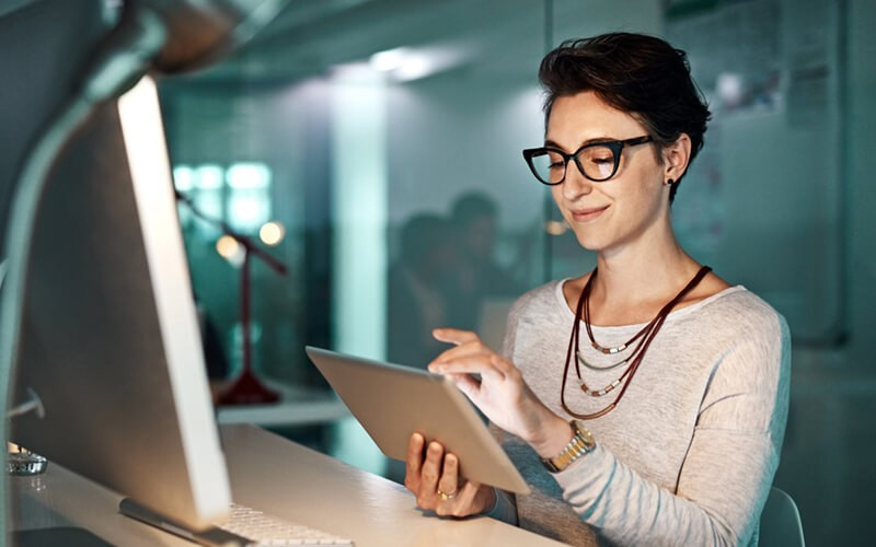 Female in glasses working from tablet